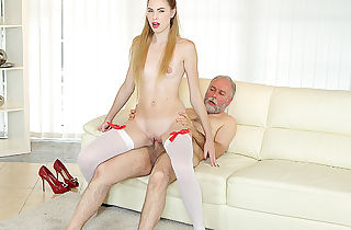 Elderly guy penetrates a uber-sexy stunner on the couch.